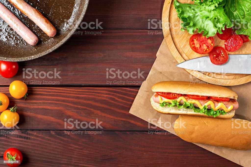Hotdog with sausage, tomatoes and salad flat lay on wooden background stock photo