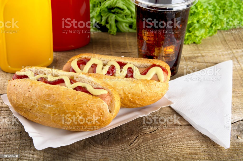 Hotdogs in the tray with ketchup,cola,lettuce on wooden stock photo