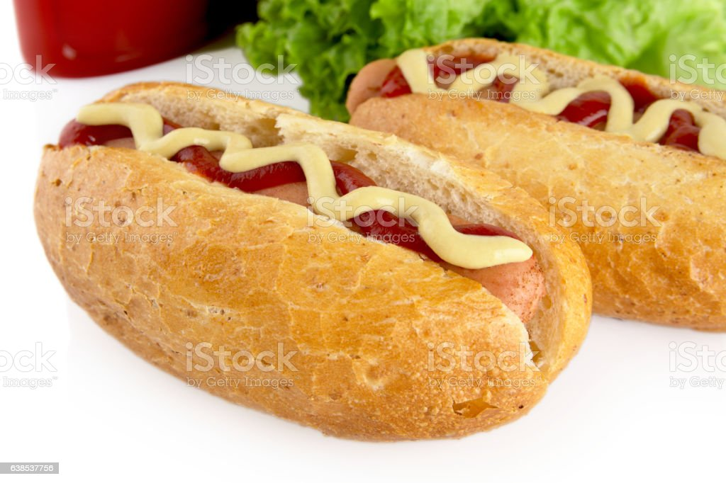 Hotdogs with ketchup with lettuce in the background on white stock photo