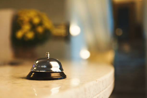 Hotel accommodation call bell on reception desk Hotel accommodation call bell on reception desk, contemporary interior, copy space inn stock pictures, royalty-free photos & images