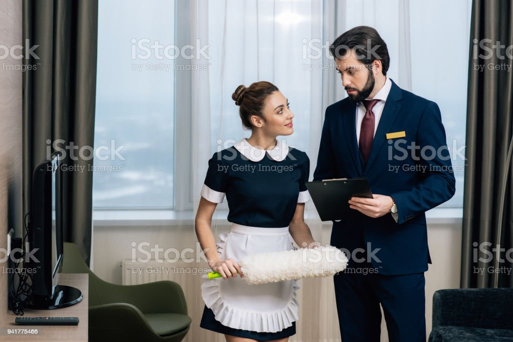 hotel administrator with clipboard talking to maid with duster at...