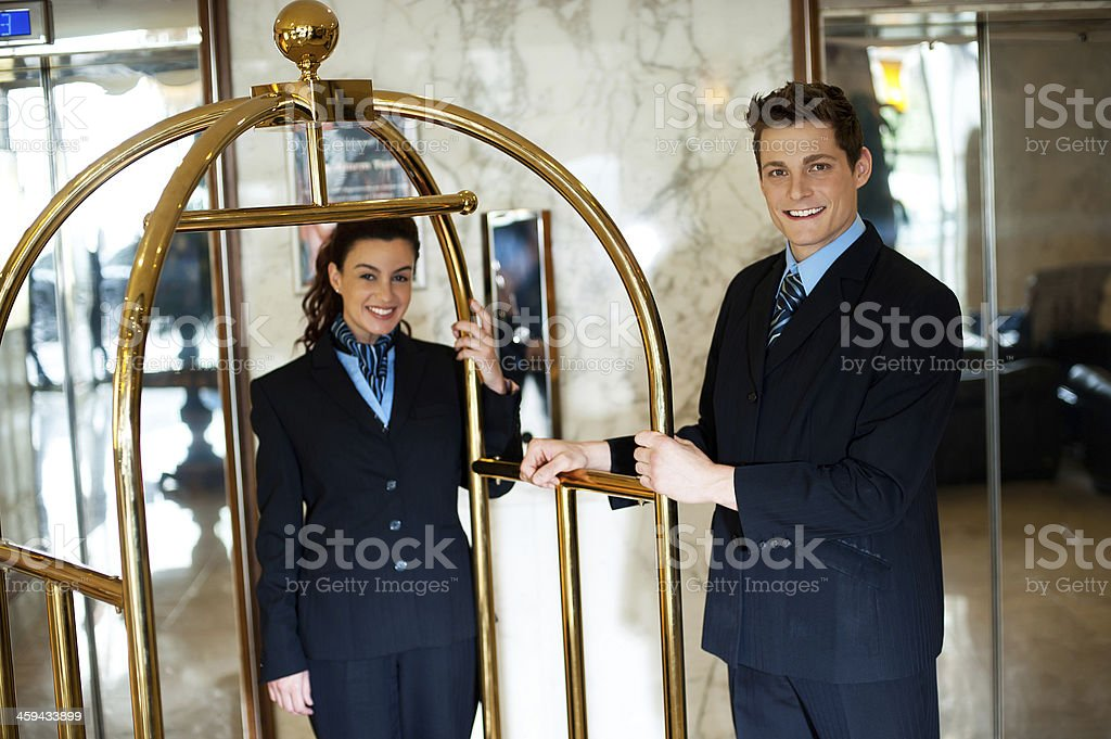 Hotel attendants posing while holding the cart stock photo