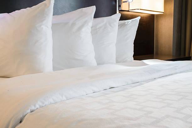 кровать в отеле - подушка стоковые фото и изображения