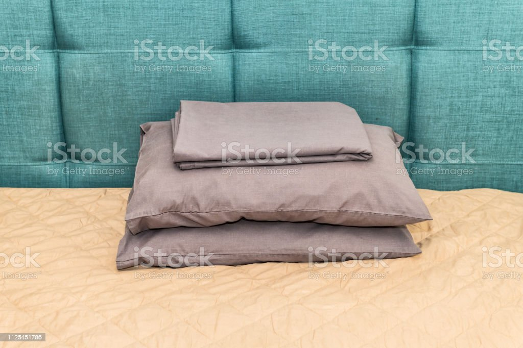 Hotel bed with green blue headboard and pillows in bedroom in home...