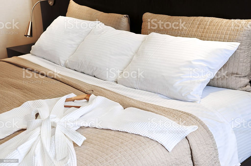 Hotel bed with white bathrobe lying on top royalty-free stock photo