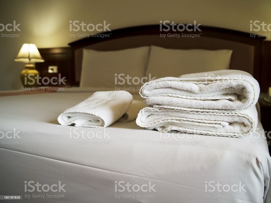 Hotel bedroom with towels on bed stock photo