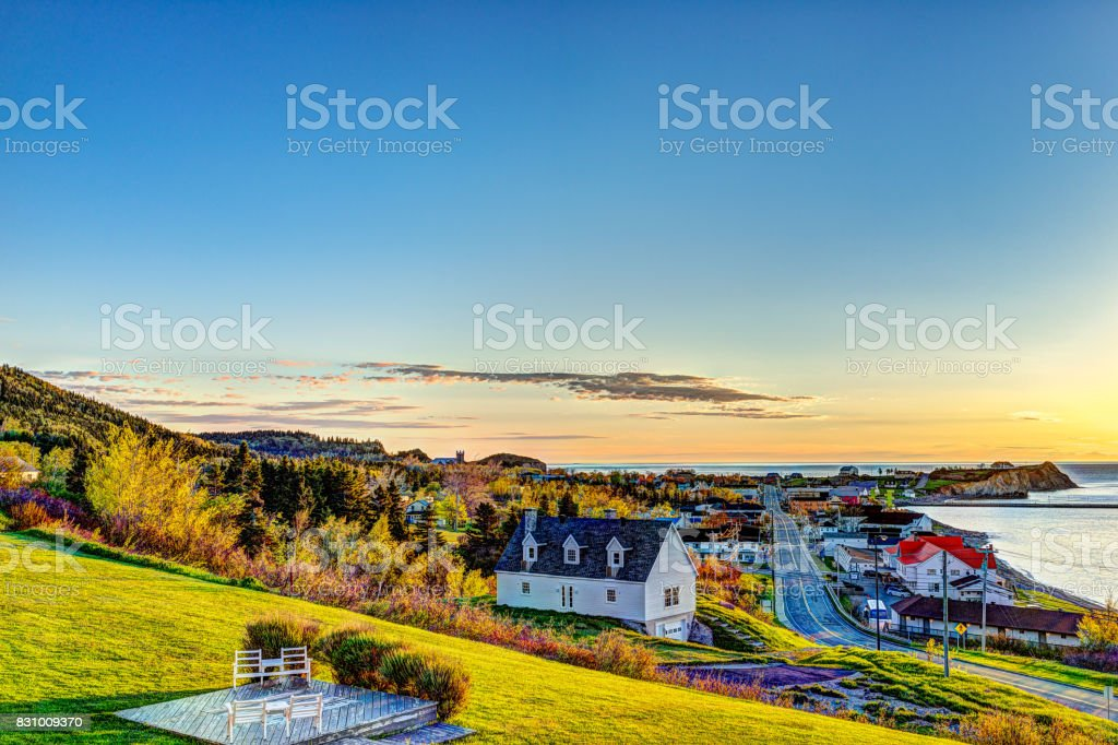 Hotel chairs on hill during sunrise in Perce, Gaspe Peninsula, Quebec, Canada, Gaspesie region with cityscape stock photo