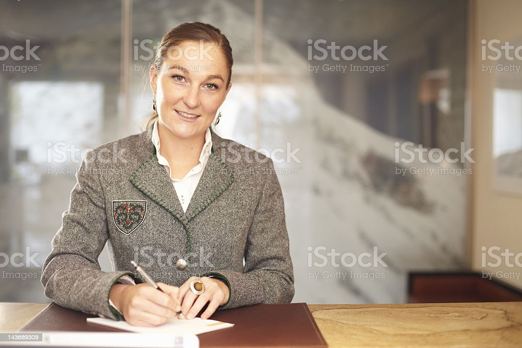 Hotel concierge writing at desk stock photo