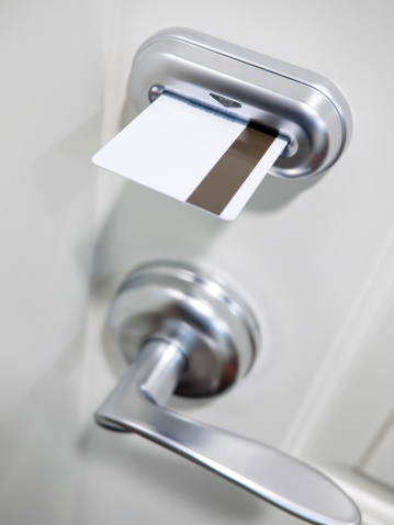 White hotel door with keycard electronic lock and handle.