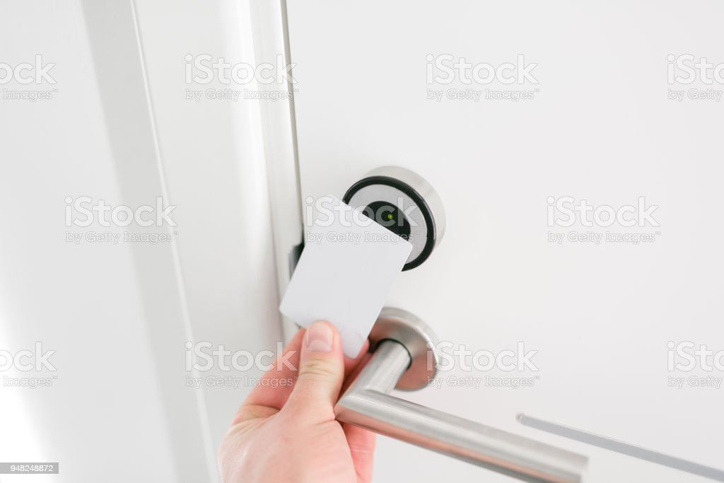Hotel door - Young man holding a keycard in front of the electronic sensor of a room door. Concept travel or business trip stock photo