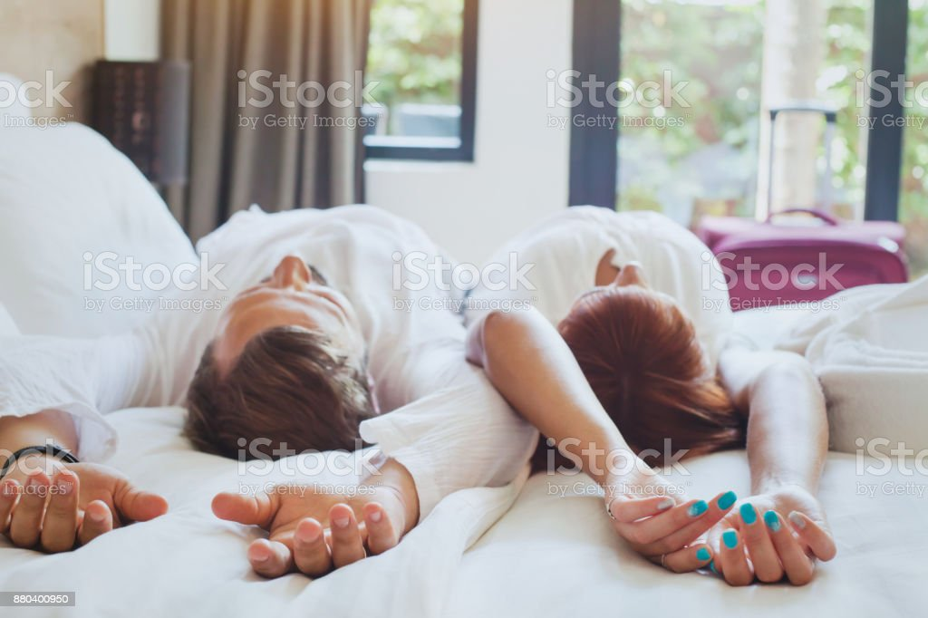 hotel guests relaxing on the bed in their room, couple traveling - foto stock
