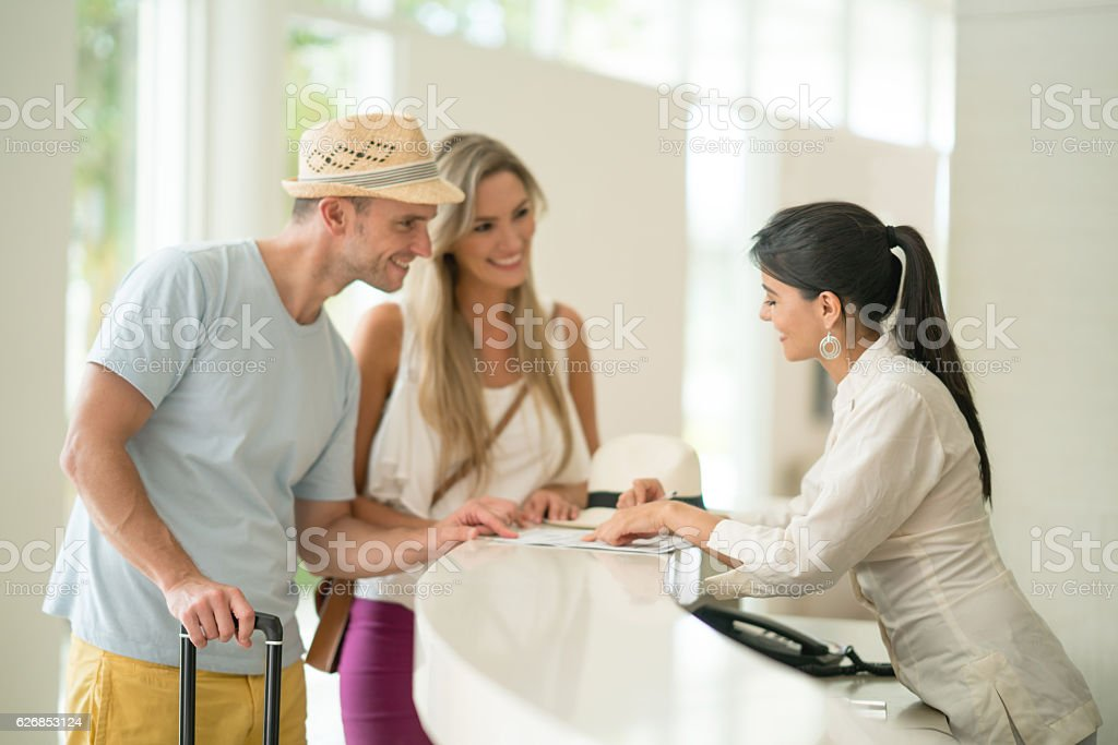 Hotel hostess helping couple with the check-in - foto de acervo