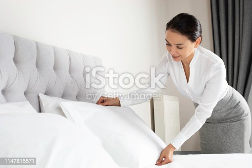 Hotel inspector is doing last checks for a bed with white sheets at a hotel.