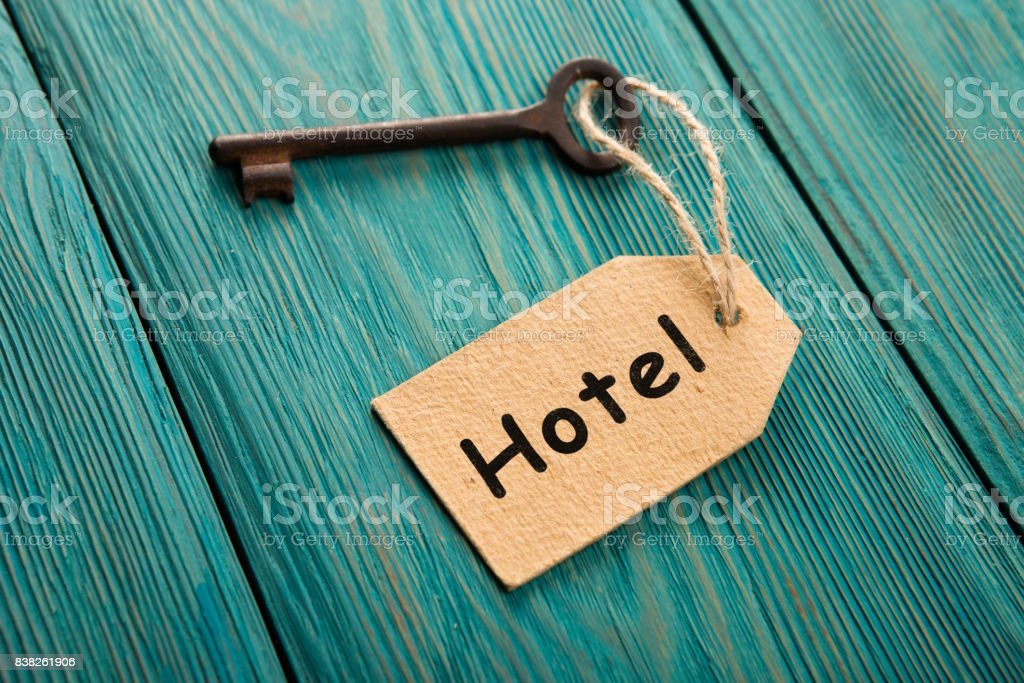 hotel key with tag on the wooden background stock photo