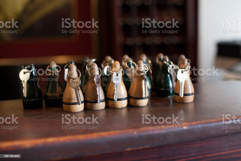 hotel keys. Keys lying on the hotel counter. Brown keys with a wooden keyring lying on the counter of the hotel and waiting for guests. stock photo