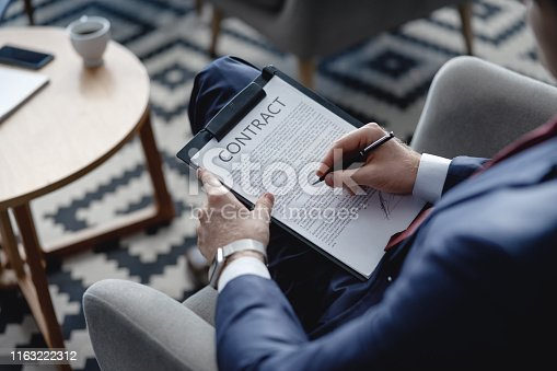 istock Hotel lobby and man holding contract on clipboard 1163222312