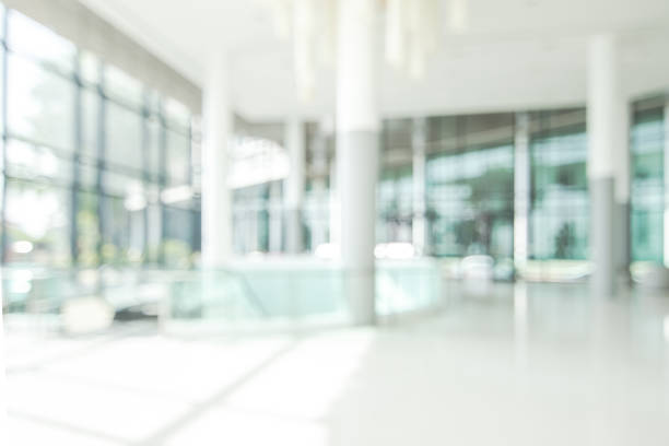 Hotel lobby blur background banquet hall interior view of luxurious foyer of empty atrium space and entrance doors and glass wall stock photo