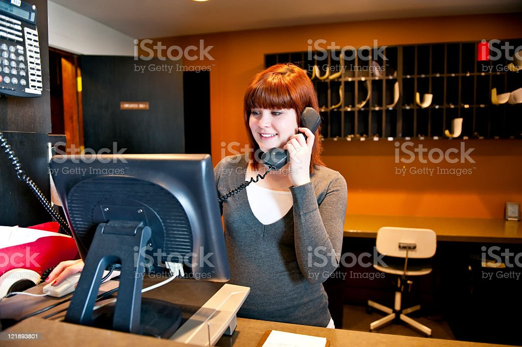 A hotel lobby receptionist on the phone royalty-free stock photo