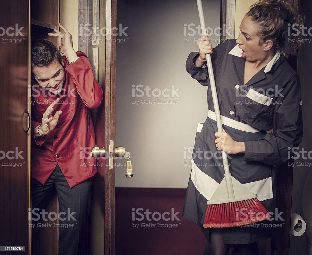 Hotel maid beating hidden porter royalty-free stock photo