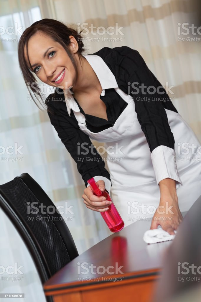 Hotel maid looking up while cleaning guest room royalty-free stock photo
