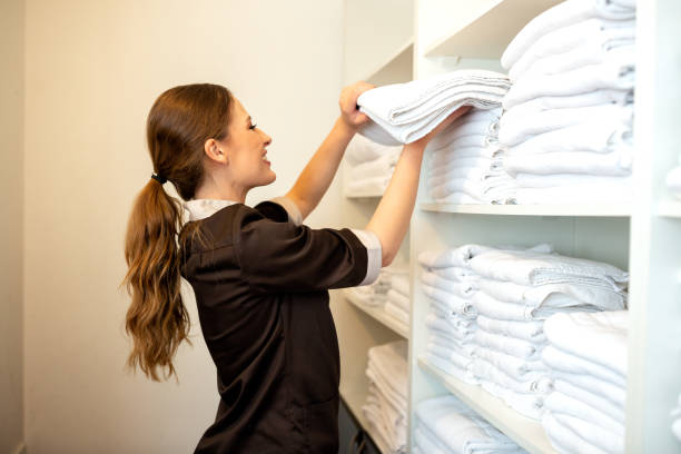 Hotel maid stacking clean sheets stock photo