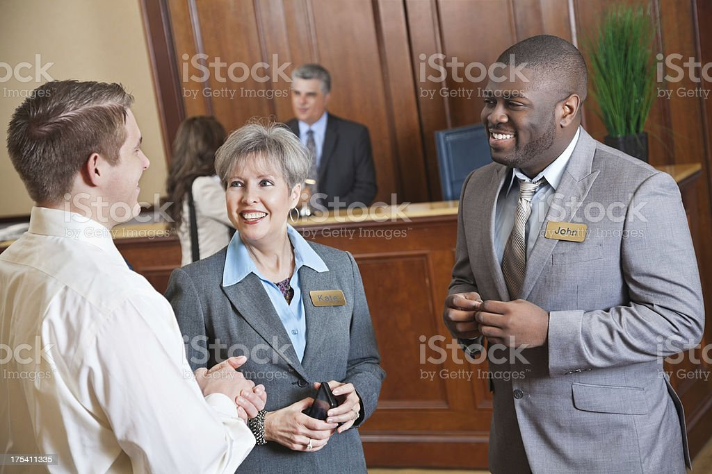 Hotel management discussing something with guest in the lobby stock photo