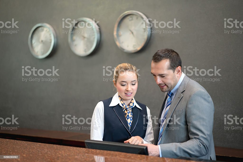 Hotel manager talking to woman at the front desk stock photo