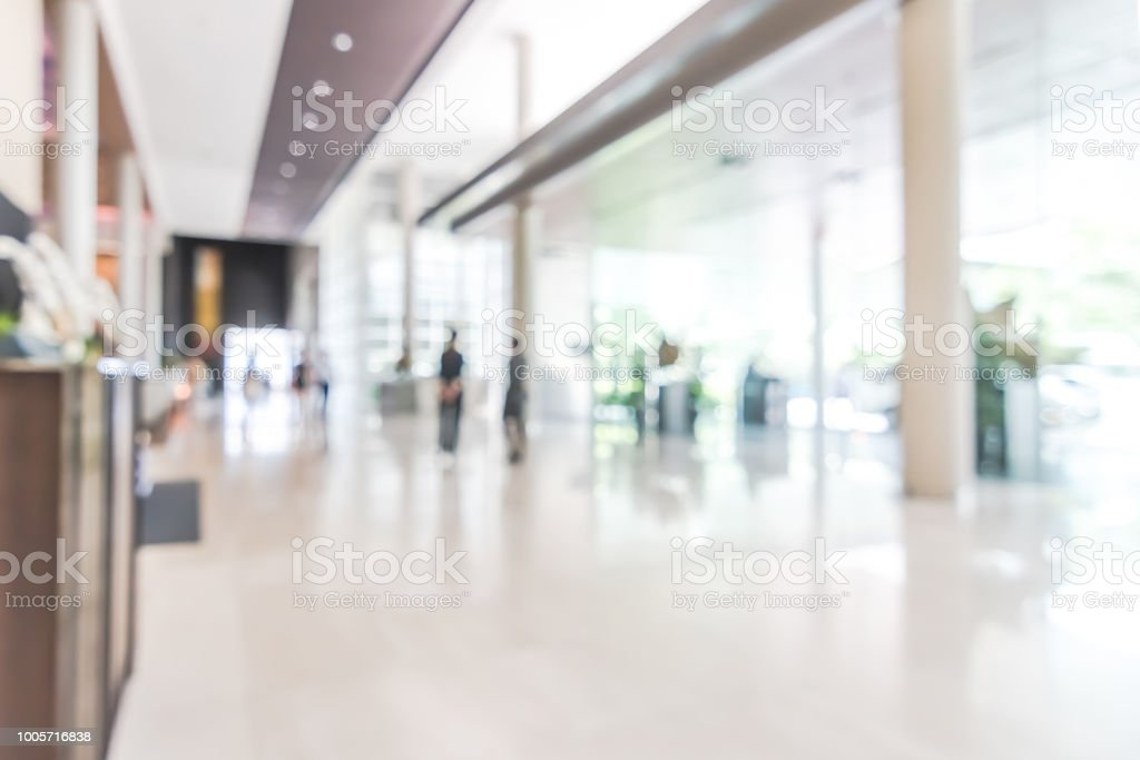 Hotel or office building lobby blur background interior view toward reception hall, modern luxury white room space with blurry corridor and building glass wall window stock photo