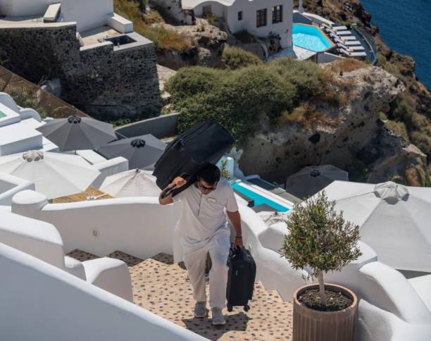 El Hotel Porter lleva el equipaje hasta el acantilado de Oia - foto de stock