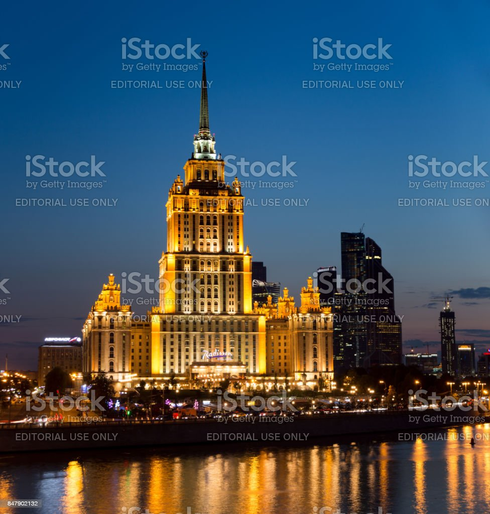 Hotel Radisson Royal (former 'Ukraine') and Moscow International Business Center 'Moscow City' - symbols of Stalin and Putin eras. Colorful lights and reflections in the Moskva River in the evening stock photo