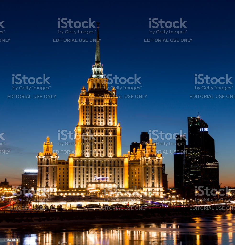 Hotel Radisson Royal (former 'Ukraine') and Moscow International Business Center 'Moscow City' - symbols of Stalin and Putin eras. Colorful lights and reflections in the Moskva River in the winter in the evening stock photo