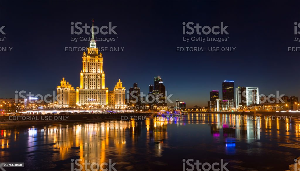 Hotel Radisson Royal (former 'Ukraine'), the Moscow International Business Center 'Moscow City' and Moscow World Trade Center - symbols of Stalin, Brezhnev and Putin eras. Colorful lights and reflections in the Moskva River in the winter in the evening stock photo