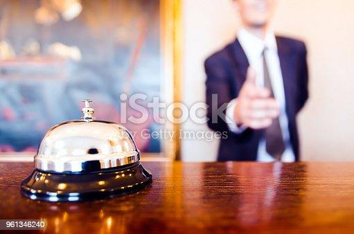 istock Hotel reception bell and receptionist greeting handshake 961346240