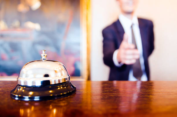 Hotel reception bell and receptionist greeting handshake Hotel reception bell and receptionist greeting handshake concierge stock pictures, royalty-free photos & images
