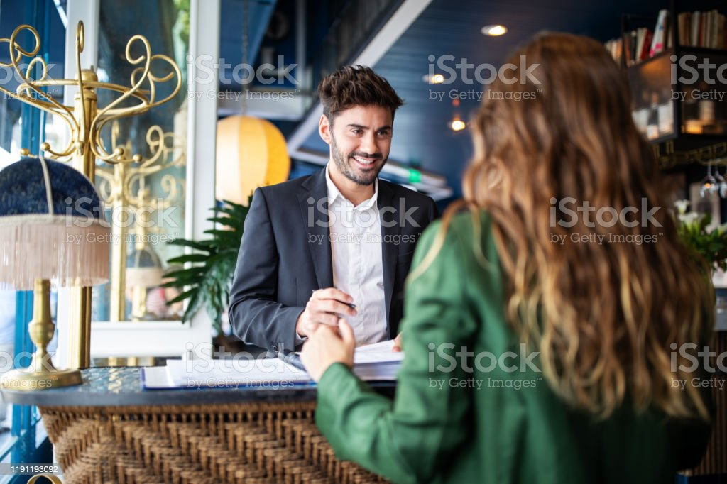 Hotel receptionist assisting guest for checking in - Royalty-free A Helping Hand Stock Photo