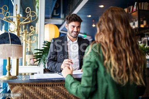 Male hotel receptionist helping a woman guest in checking in process. Woman in hotel check-in at reception talking with the concierge at front office.