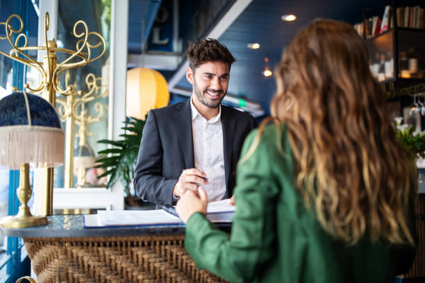 Hotel receptionist assisting guest for checking in Male hotel receptionist helping a woman guest in checking in process. Woman in hotel check-in at reception talking with the concierge at front office. service stock pictures, royalty-free photos & images