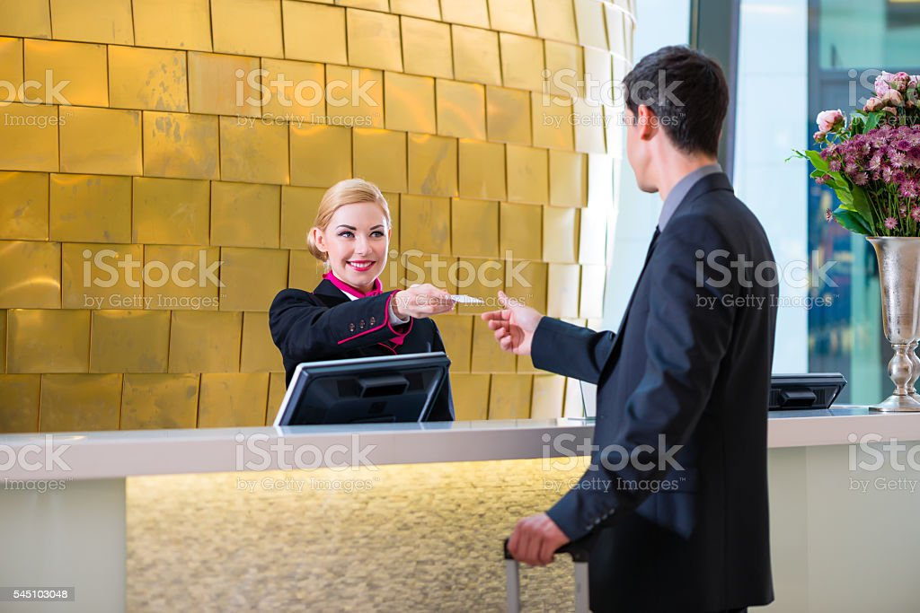 Hotel receptionist check in man giving key card - Photo