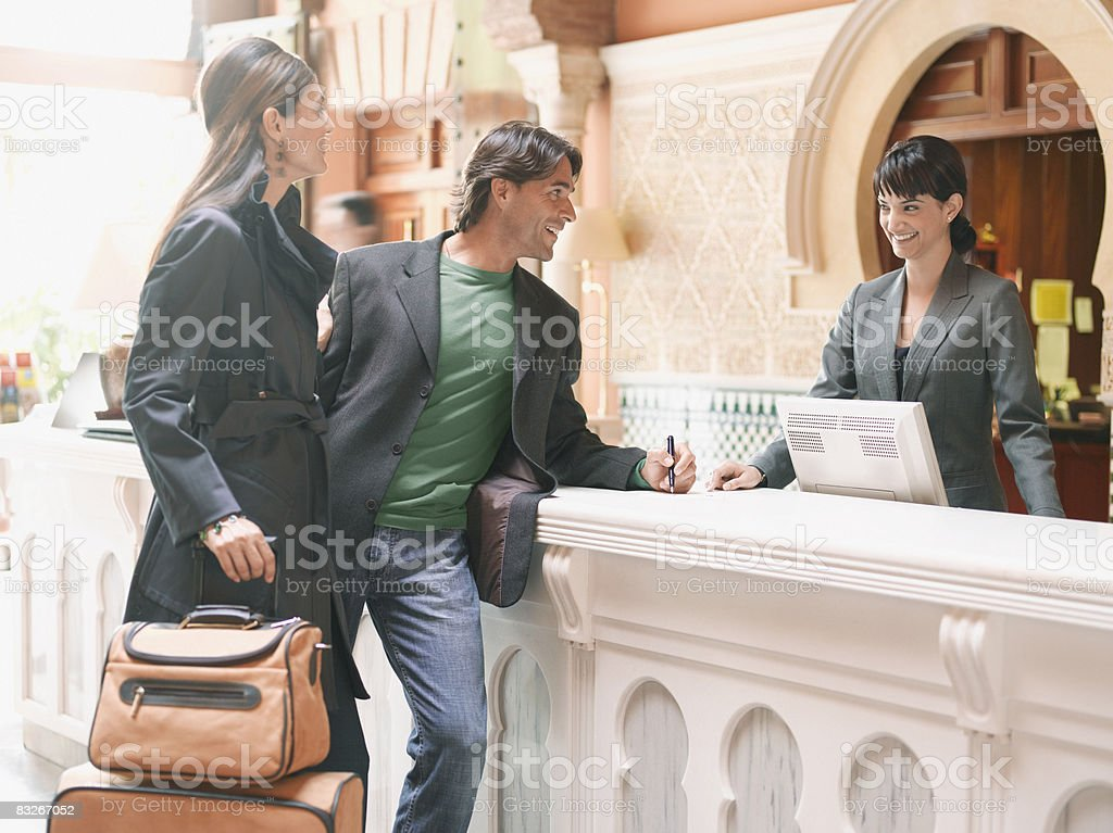Hotel receptionist checking couple in royaltyfri bildbanksbilder