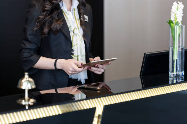 Hotel Receptionist checking up room status on digital tablet Hotel Receptionist checking up room status on digital tablet concierge stock pictures, royalty-free photos & images