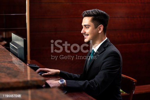 Hotel receptionist executing administrative tasks to the highest quality standards