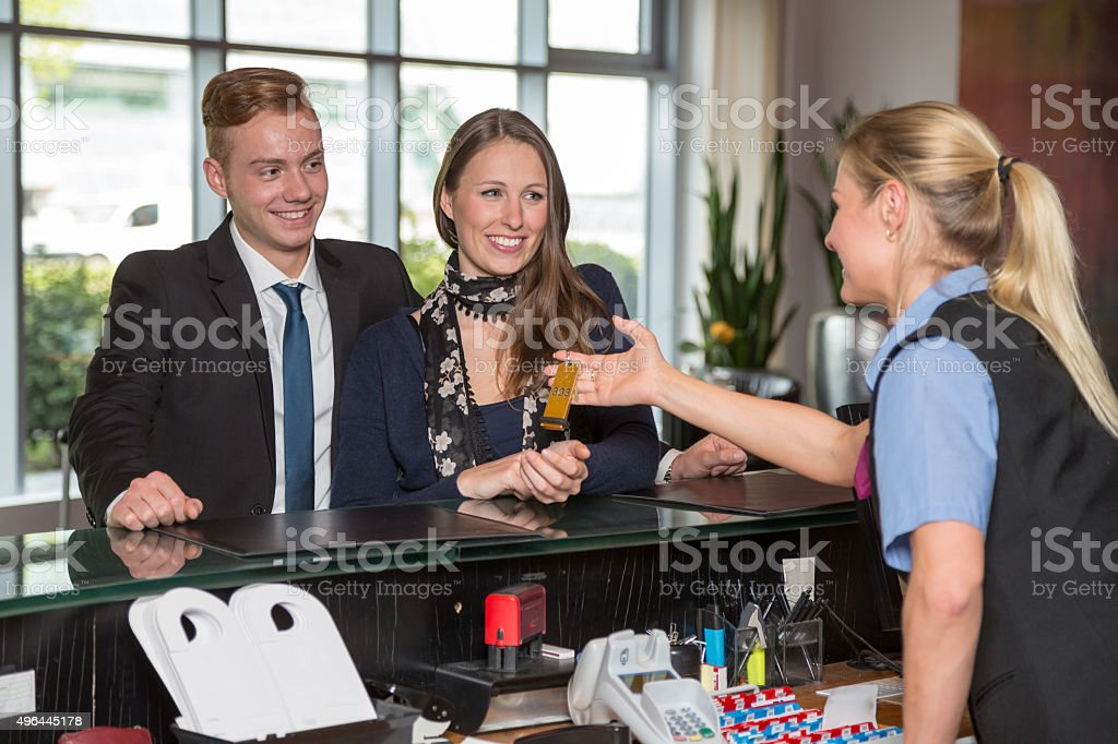 Hotel receptionist handing over key to customers stock photo