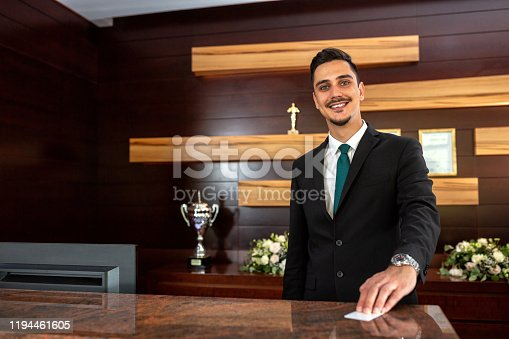 Hotel receptionist offering a key card, guest management system