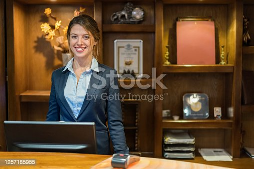 Portrait of smiling hotel receptionist standing at her workplace