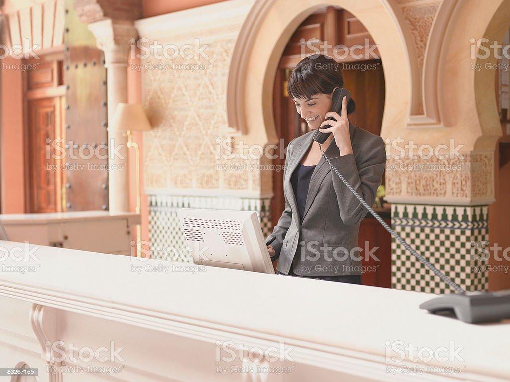 Hotel Recepcjonista rozmawia przez telefon zbiór zdjęć royalty-free