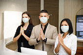 hotel receptionist wearing mask to protect from conronavirus covid 19 having new practice of greeting with thai wai, new greeting practice in coronavirus covid 19 pandemic