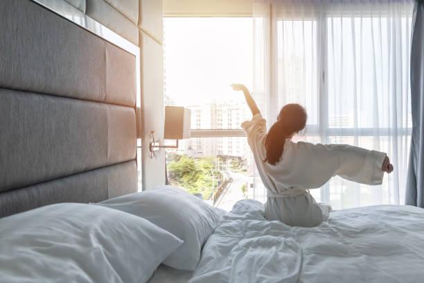 confort de chambre d'hôtel avec le bon sommeil mode de vie facile de relaxation de fille asiatique sur le lit ont une belle journée matin a réveiller, prendre un peu de repos, paresseusement se détendre dans la chambre d'hôtes dans l'hôtel de ville - hôtel photos et images de collection