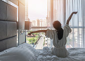 istock Hotel room comfort with good sleep easy relaxation lifestyle of Asian girl on bed have a nice day morning waking up, taking some rest, lazily relaxing in guest bedroom in city hotel 1257109841
