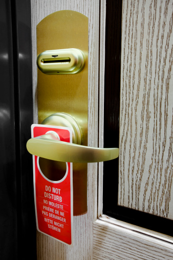 A hotel room door with a Do Not Disturb sign.