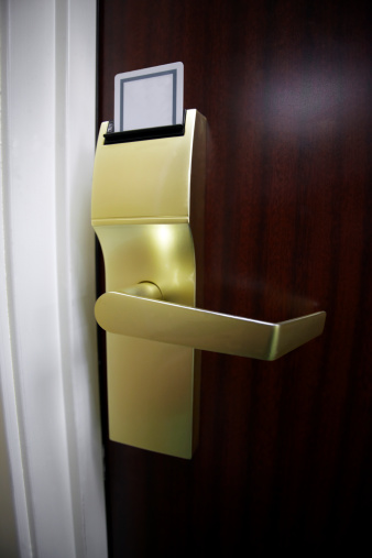 Vertical stock photo of a hotel room electronic door lock and keycard.